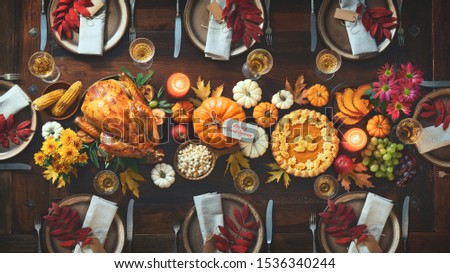 Thanksgiving celebration traditional dinner. Roasted turkey garnished with cranberries on a rustic style table decoraded with pumpkins, vegetables, pie, flowers and candles. Festive table setting #1536340244