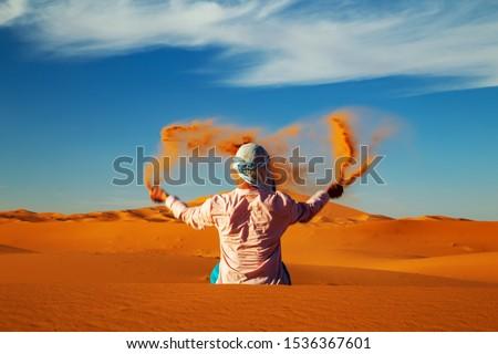 Single Man throws sand in the Sahara desert at sunset. Erg Chebbi, Merzouga,  Morocco. Royalty-Free Stock Photo #1536367601