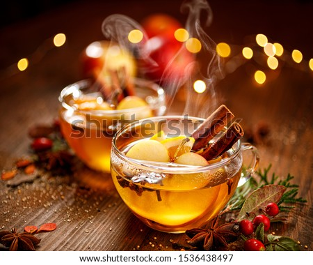 Mulled cider with slice apples, cinnamon, cloves, anise stars and citrus fruits in glass cups on a wooden rustic table, close-up. Delicious,  traditional hot drink #1536438497