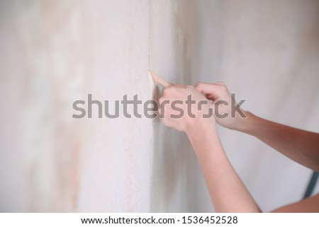 woman tears off Wallpaper, removing Wallpaper from the wall with a spatula, the process of updating the wall room repair. with free text space #1536452528