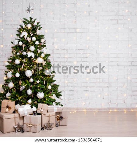 decorated christmas tree, heap of gift boxes and copy space over white brick wall background #1536504071