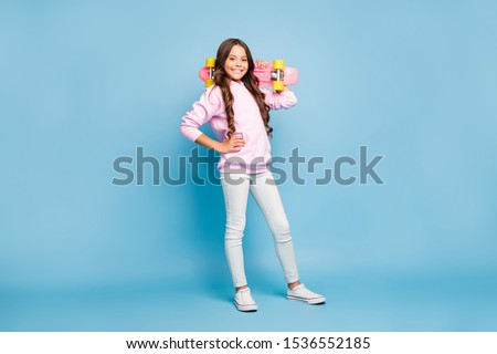 Turned full length body size photo of cheerful pink positive girl holding skate board on her shoulder wearing footwear isolated pastel blue color background #1536552185