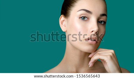 Beautiful young  woman with clean perfect fresh skin touching her face. Portrait of beauty model with natural make up, formed eyebrows  and long eyelashes.  Spa, skincare and wellness. Royalty-Free Stock Photo #1536565643