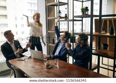 cheerful young office workers celebrating their successful contract in the office with modern interior. close up photo #1536566345
