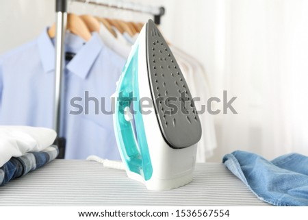 Iron and shirt on ironing board, space for text #1536567554