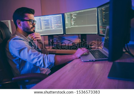 Profile photo of it specialist guy sitting comfy office chair holding hand on keyboard looking many monitors checking website debugging expert dark office indoors Royalty-Free Stock Photo #1536573383