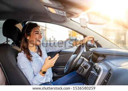Woman driver using a smart phone in car. Woman driver using a smart phone in car. Leisure, road trip, technology, travel and people concept - Happy woman driving car with smarhphone #1536580259