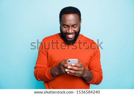 Photo of cheerful positive handsome man holding telephone smiling toothily searching information new isolated vivid blue color background