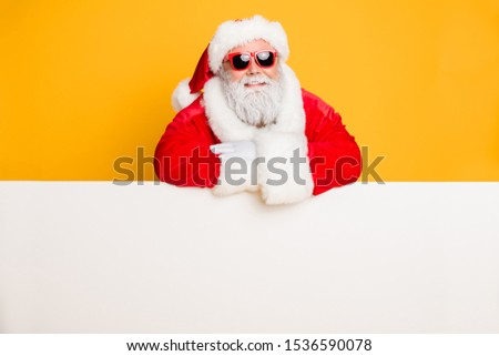 Portrait of funky funny santa claus put hands on white pure billboard advertise winter shopping season x-mas sales fairy discounts isolated over yellow color background #1536590078