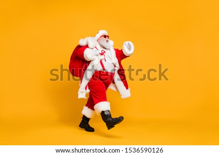 Full size profile side photo of funky fat santa claus with huge abdomen hold gift wish bag go walk travel around world on christmas night eve wear x-mas hat suspenders isolated bright color background #1536590126