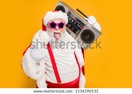 Portrait of fat white hair funny santa claus heavy metal x-mas hipster party hard on noel celebration show horns sign hold retro boombox wear trendy hat suspenders isolated yellow color background #1536590132