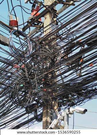 Many electrical cable, wire, telephone line and CCTV on electricity pole, The chaos of cables and wires on every street in Bangkok, Thailand. #1536590255