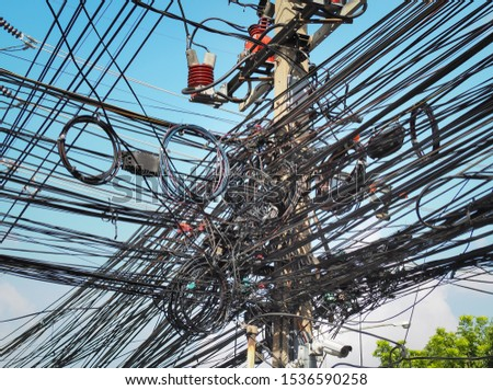 Many electrical cable, wire, telephone line and CCTV on electricity pole, The chaos of cables and wires on every street in Bangkok, Thailand. #1536590258