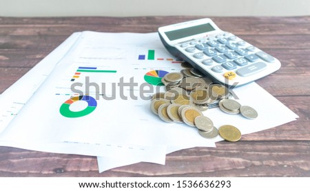 Line graphs, pie graphs, and graphs of various colors printed on white paper Placed on a wooden patterned work desk Complete with a calculator and a pile of Thai baht coins #1536636293