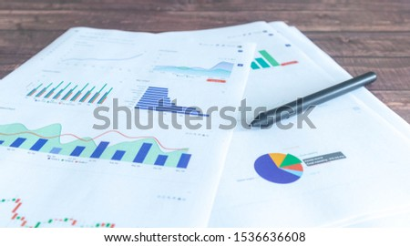 Line graphs, pie graphs, and graphs of various colors printed on white paper Placed on a wooden patterned work desk #1536636608