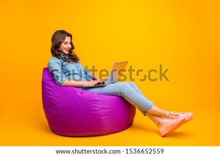 Full length body size turned photo of cheerful positive cute nice attractive blogger browsing through her laptop in search of new information isolated over yellow vibrant color background #1536652559
