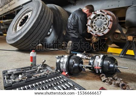 Truck repair service. Mechanic works with brakes in truck workshop #1536666617