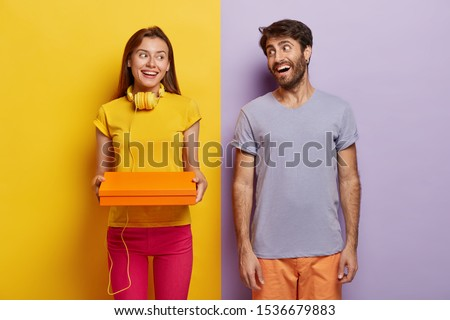 Happy woman and man satisfied after successful shopping day, hold small box, dressed in casual outfit, stand indoor against yellow and purple background. Girlfriend prepares surprise to boyfriend #1536679883