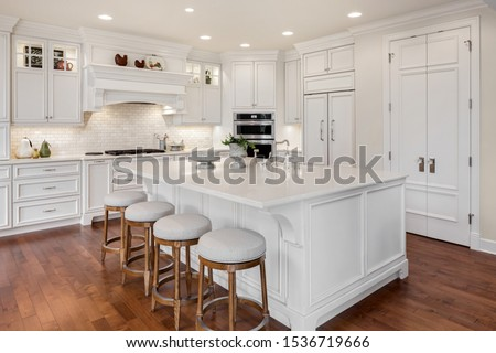 Beautiful kitchen in new traditional style luxury home. Features white island, counters, and cabinetry, and dark hardwood floors Royalty-Free Stock Photo #1536719666