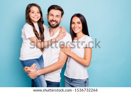 Portrait of positive cheerful mommy daddy carry kid feel content enjoy weekends wear white t-shirt denim jeans isolated over blue color background