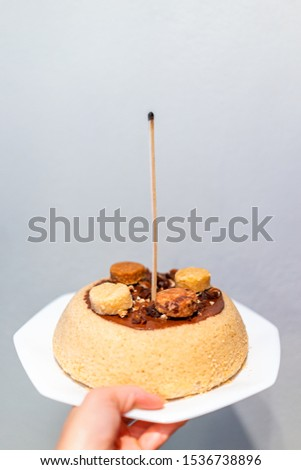 Hand holding one yellow vanilla homemade sponge cake with chocolate sauce and macaroon decoration with candle match stick for birthday #1536738896