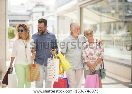 two couples of two adults and two seniors go shopping together at the mall with a lot of bags with clothes and more on their hands - four people happy enjoying #1536746873