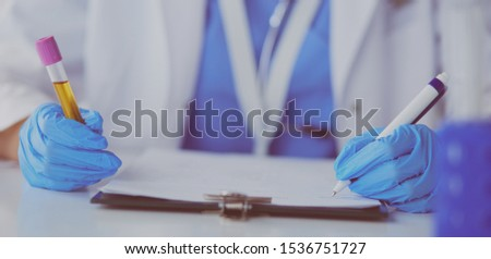 Woman researcher is surrounded by medical vials and flasks, isolated on white background #1536751727