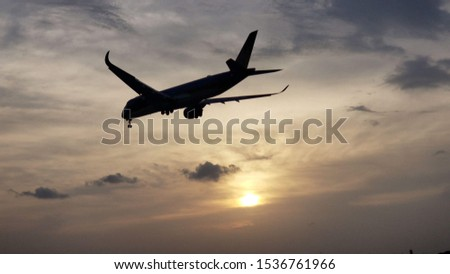A photo of a Vietnam Airline. A350 silhouette with the sunset in the background.