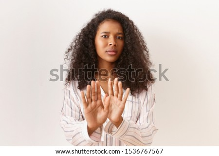 Portrait of frustrated young Afro American female with curly hair having frightened facial expression, scared, making Stop gesture with hands reached out. Refusal, denial and rejection concept #1536767567
