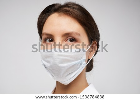 Head and shoulders portrait of female doctor wearing protective mask and looking at camera posing against white background #1536784838