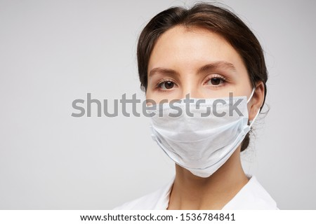 Head and shoulders portrait of female doctor wearing protective mask and looking at camera posing against white background, copy space #1536784841