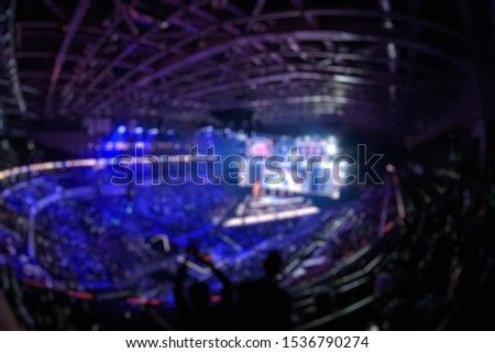 Blurred background of an esports event - Big illuminated main stage of a computer games tournament located on a big stadium. Tribunes are full of video games fans. #1536790274