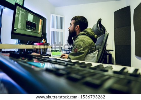 Young DJ with long beard is producing electronic music in his studio. #1536793262