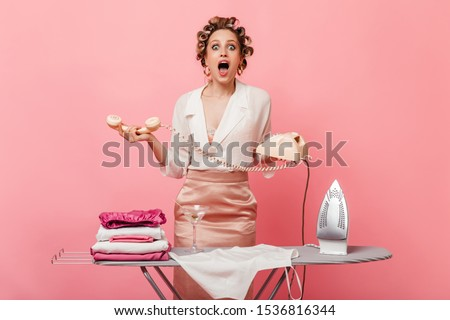 Lady with hair curlers looks amazed at cameo. Girl holding landline phone and posing with ironing board #1536816344