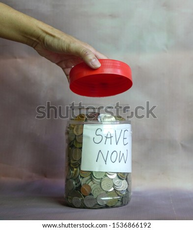 Savings concept. Coins saved inside container with Save Now words written on paper. #1536866192