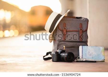 Backpack travel with hat, camera, map, earphone and smart phone on the ground of train station at sunset background train. travel and backpack concept. #1536904724