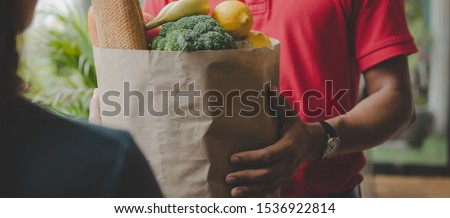 panoramic banner. smart food delivery service man in red uniform handing fresh food with young woman customer receiving order from courier at home, express food delivery and shopping online concept #1536922814