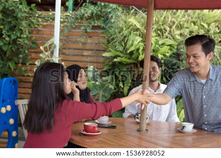 Happy multiracial Asian young people hang out outdoors together give high five greeting, smiling diverse multiethnic millennial friends join hands celebrating shared win or gather for meeting #1536928052
