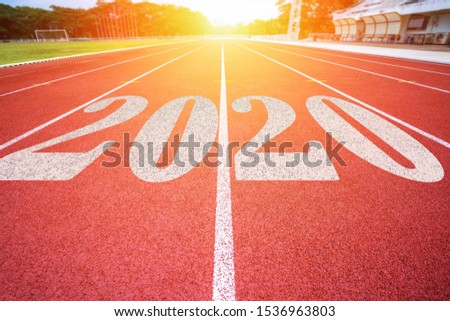 White lines of stadium and texture of running racetrack red rubber racetracks with 2020 Happy New Year text,During Christmas and New Year. #1536963803