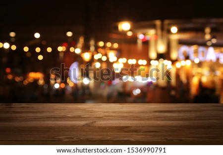 background Image of wooden table in front of abstract blurred restaurant lights #1536990791