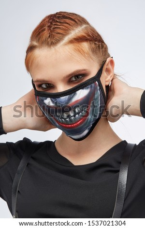 Close-up portrait of a ginger girl with three french braids, posing on a grey background. She's wearing black sweatshirt and leather belt. Her face is hidden by mask with Joker smile print.