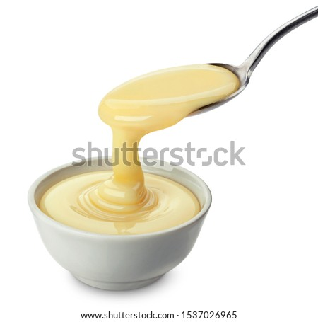 Pouring condensed milk with spoon isolated on white background with clipping path, delicious flowing creamy evaporated cream Royalty-Free Stock Photo #1537026965