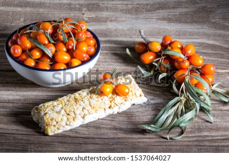 Energy bar with sea buckthorn berries on a wooden background. Sea buckthorn berries on a branch and in a white Cup. #1537064027