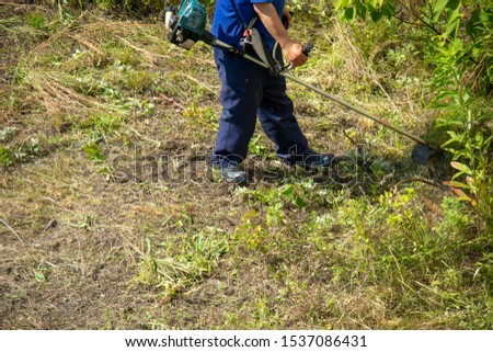 Worker man mowing grass with mower #1537086431