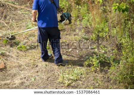 Worker man mowing grass with mower #1537086461