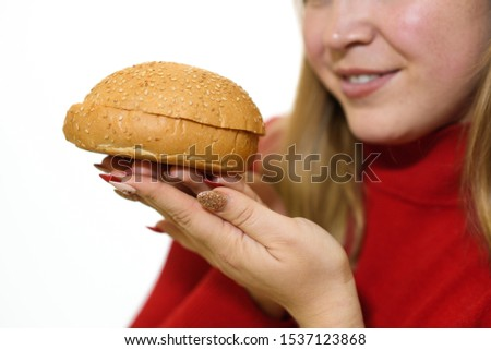 Fat girl on a white background holds a burger. Close-up shot. Studio shot. #1537123868