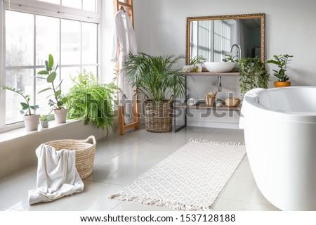 Stylish interior of bathroom with green houseplants Royalty-Free Stock Photo #1537128188