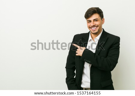 Young business hispanic man smiling and pointing aside, showing something at blank space. #1537164155