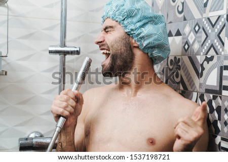 Attractive young cheerful man singing while washing in the shower, wearing shower cap and holding shower head Royalty-Free Stock Photo #1537198721