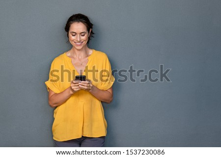 Smiling mature woman using smartphone isolated on gray wall with copy space. Happy latin woman in casual typing on cellphone over grey background. Portrait of cheerful middle aged lady messaging. Royalty-Free Stock Photo #1537230086